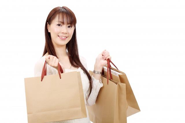 両手に複数の紙袋を持つ女性