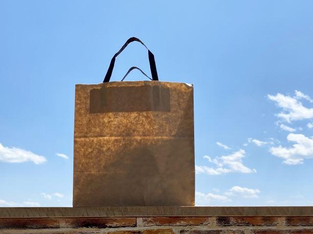 空を背景に一つの紙袋